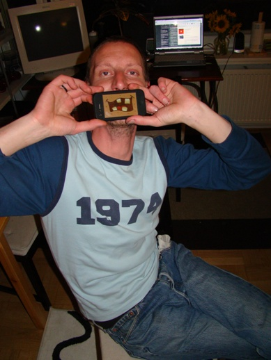 A Belgian guy fooling around with his iPhone at Serkan's and Funda's housewarming party